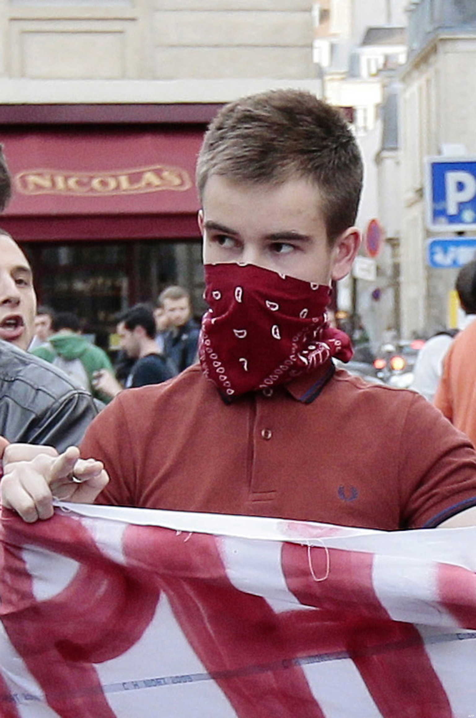 "A photo taken on April 17, 2013, in Paris, shows Clement Meric, a student at the city's prestigious Sciences-Po university and a left-wing activist, wearing a bandana over his face as he holds a banner reading ""Homophobia kills"" and faces riot policemen while supporters of the anti-gay marriage movement ""La Manif Pour Tous"" (Demonstration for all!) demonstrate, a few hours after the second reading of France's landmark bill allowing gay marriage at the French National Assembly. Clement Meric, 18, a left-wing French activist died on June 6, 2013, after a fight with skinheads in Paris, sparking concern over the rise of extreme-right groups, as police grilled seven people over the tragedy. AFP PHOTO / JACQUES DEMARTHON"